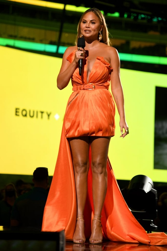 Chrissy Teigen in an orange creation at the Vax Live concert with her daughter Luna